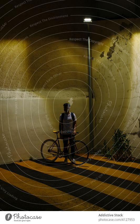 Unbekannter Mann mit Fahrrad bei Nacht Fixie Zyklus urban Rad feststehend Sport Transport Ausrüstung Lifestyle Wand Straße Hipster Mitfahrgelegenheit Pedal