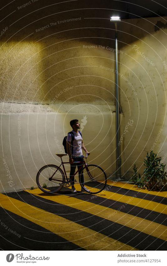 Mann schaut auf die Straßenlaterne mit einem Fahrrad Fixie Zyklus urban Rad feststehend Sport Transport Ausrüstung Lifestyle Wand Hipster Mitfahrgelegenheit
