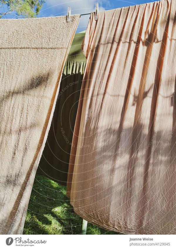 Kleider und Handtuch hängen an einem sonnigen Nachmittag auf einer Wäscheleine. Gras und Himmel. Waschtag Wäscherei Haushalt Kleiderhaken Haushaltsführung