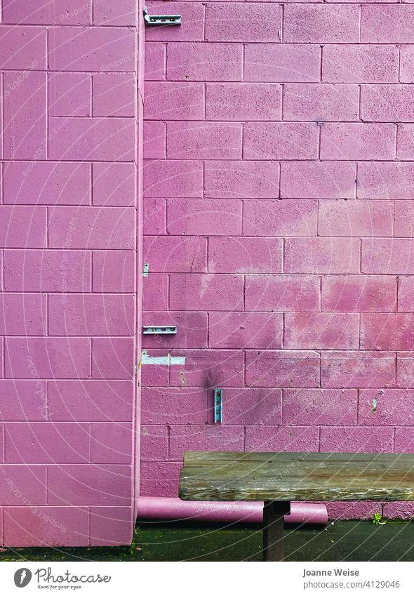 Rosa Ziegelwand mit braunem Sitz. rosa rosa Hintergrund rosa Wand grobkörnig Backsteinwand Baustein Sitzgelegenheit Außenaufnahme Mauer Fassade alt