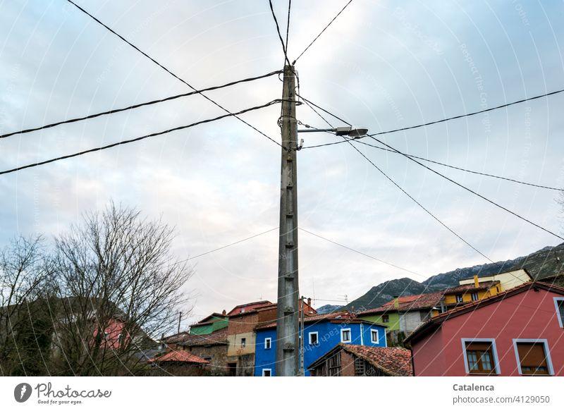 Straßenlaterne, Stromkabel, ein buntes Dorf, kahle Bäume an einem Wintermorgen. Straßenbeleuchtung Strommast Straßenlampe Energie Energieverteilung Himmel