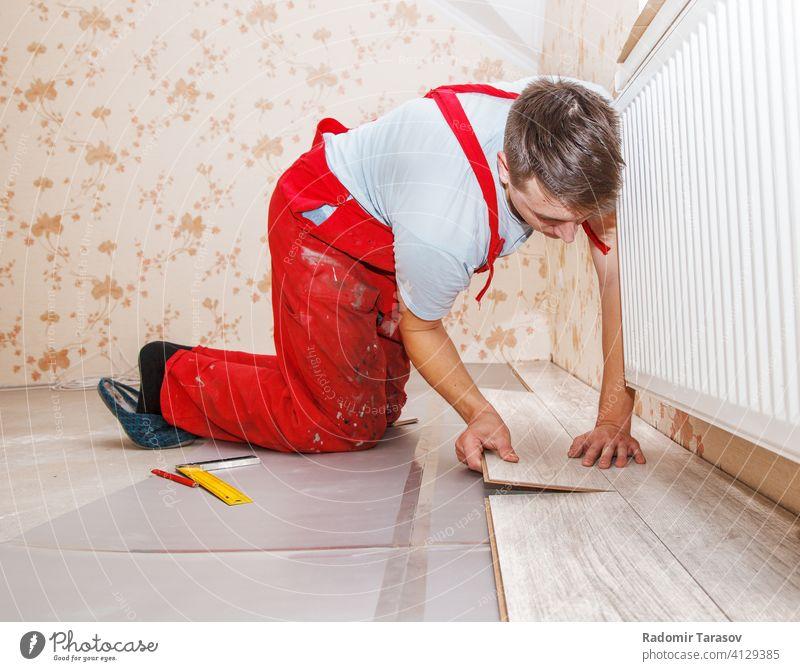 Junger Handwerker verlegt Holzboden Panel heimwärts Bodenbelag im Innenbereich Stock kaschieren Verlegung Renovierung Dekoration & Verzierung Parkett