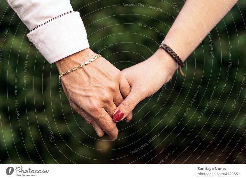 Paar hält Hände Nahaufnahme abschließen Partnerschaft Händchenhalten Zusammensein lieblich Liebe Vorderansicht Hintergrund zwei Familie im Freien außerhalb Park