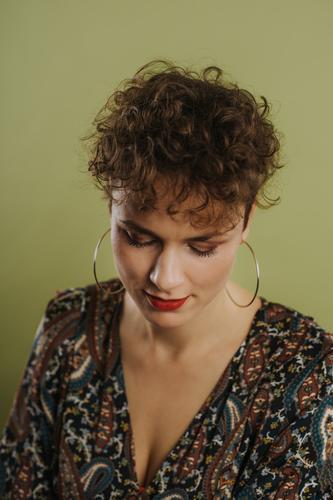Porträt einer nach unten schauenden Frau Erwachsener schön Schönheit Freizeitkleidung Selbstvertrauen selbstbewusst Kräusel krause Haare Ohrringe Vorderansicht