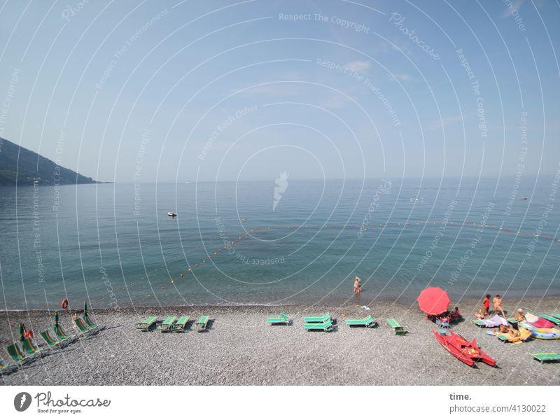 Morgenbad strand meer Mittelmeer Liegestühle sonnenschirm berg ruhig reisen sonnig diesig urlaub ferien baden italien morgensonne horizont himmel fernweh
