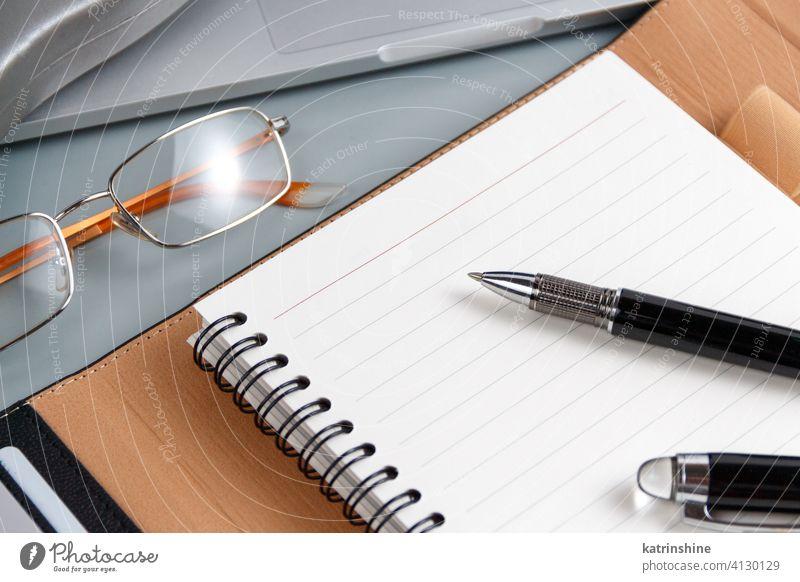 Geöffnete Agenda und Stift auf einer grauen Nahaufnahme Business aufgeklappt schreiben Laptop Planer Schreibstift Büro Schreibtisch abschließen Brille