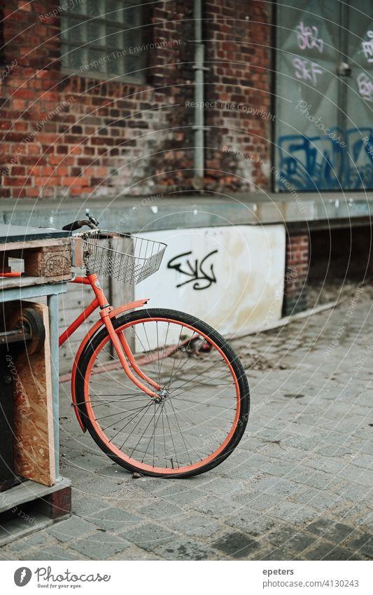 Orangefarbenes Fahrrad in einem industriellen Lagerhausviertel in Hamburg Deutschland Oberhafen Backsteinwand Arbeitsweg dreckig grau industrieller Stil orange