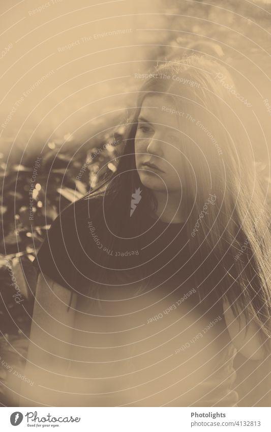 Junge Frau mit langen Haaren blickt zur Seite jung Porträt lange Haare Garten monochrome hübsch attraktiv Mädchen Haare & Frisuren Außenaufnahme Erwachsene