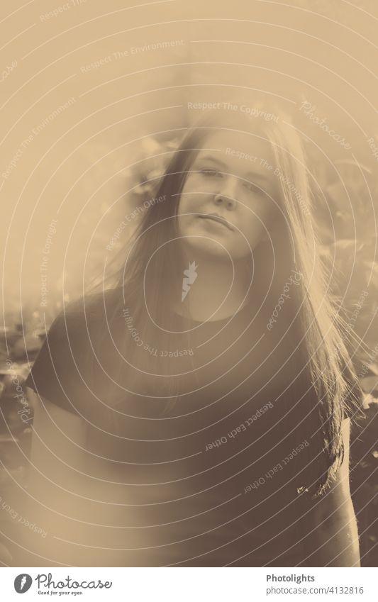 Junge Frau mit langen Haaren blickt in die Kamera jung Porträt lange Haare Garten monochrome hübsch attraktiv Mädchen Haare & Frisuren Außenaufnahme Erwachsene