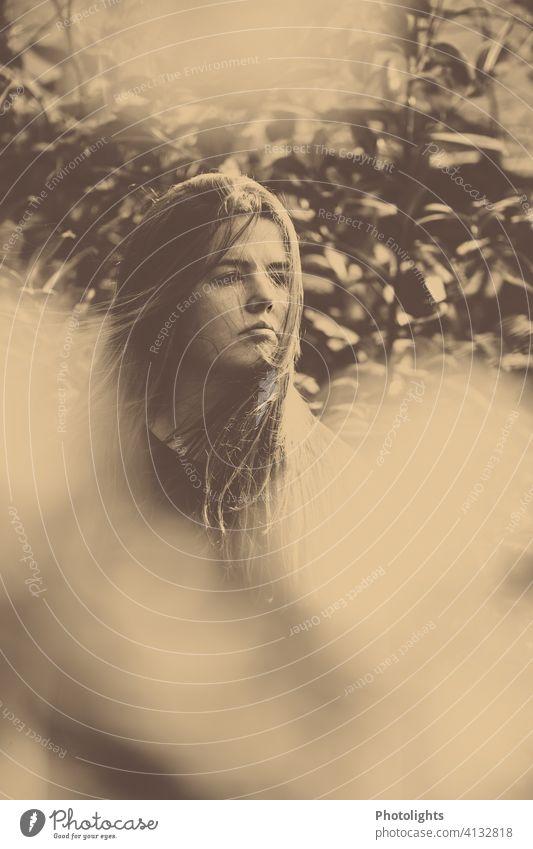 Junge Frau mit langen Haaren blickt suchend in die Ferne. jung Porträt lange Haare Garten monochrome hübsch attraktiv Mädchen Haare & Frisuren Außenaufnahme