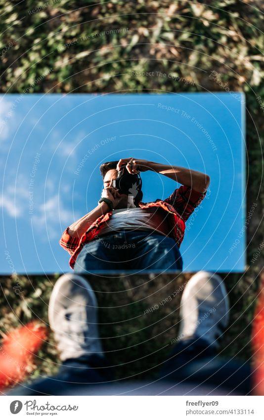Junger Fotograf nimmt ein Selfie auf jung Mann Spiegel Porträt Selbstportrait Hintergrund abstrakt Himmel Gras Attrappe Textfreiraum Rechteck Wolken Natur Licht