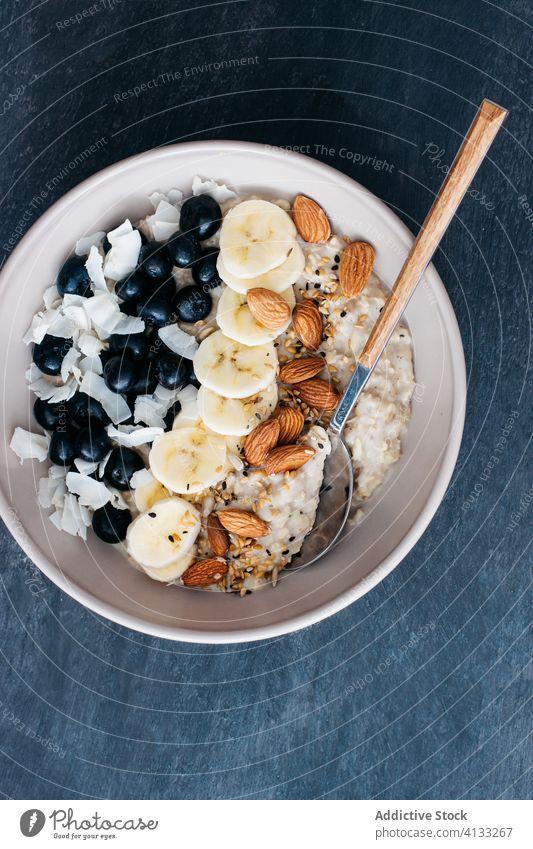 Schale mit Haferbrei Blaubeeren Mandeln Banane Kokosnuss Saatgut Löffel Korn Frucht Haferflocken Lebensmittel Frühstück Schalen & Schüsseln Gesundheit Müsli