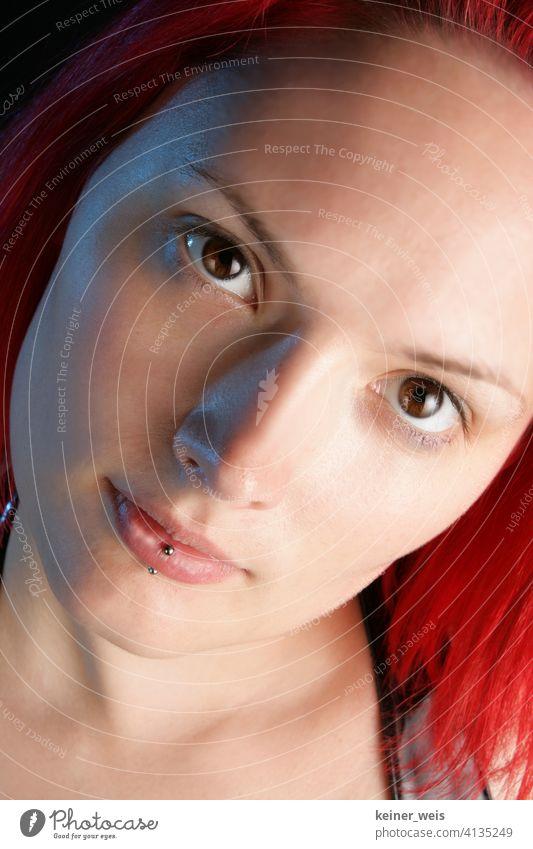 Gesicht einer jungen Frau mit Piercing in der Unterlippe und rotem Haar Junge Frau braune Augen rothaarig rotes Haar hochformat Portrait Porträt Lippenpiercing