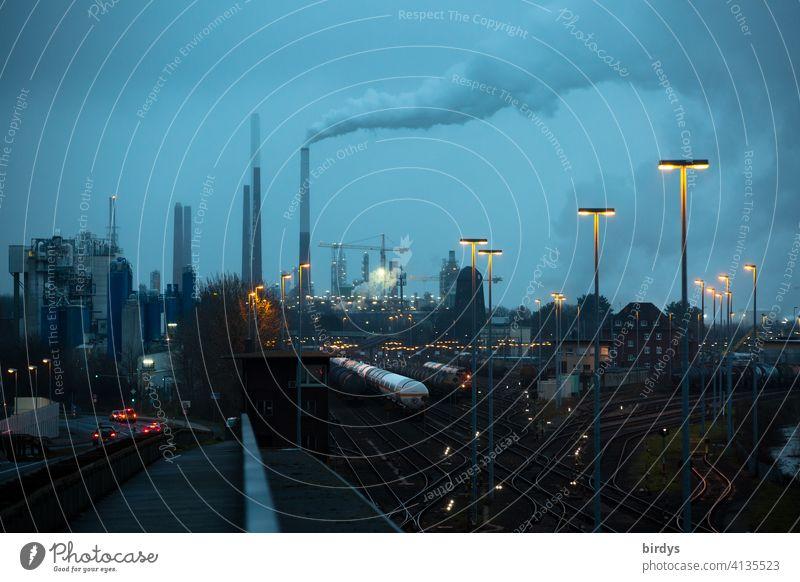 Industrielandschaft mit Güterzügen, Industrieanlagen und Beleuchtung zur blauen Stunde. Industrie, Logistik, Schienenverkehr Industriefotografie Chemieindustrie