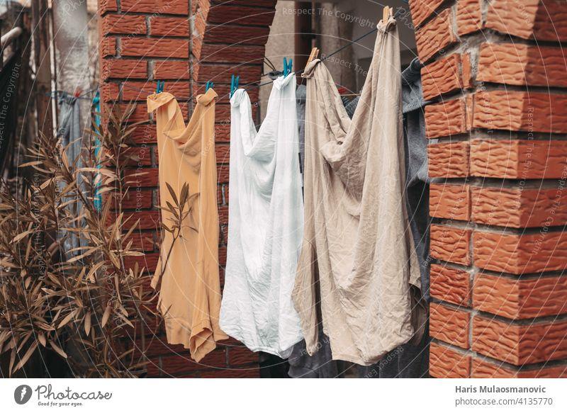 gewaschene Kleidung Männerhemden hängen vor dem Haus orange gelb Pastell Baby Säuglingsalter Hintergrund blau Kinderbetreuung Kindheit Sauberkeit Stoff