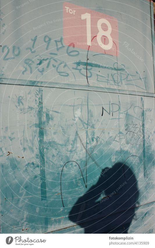 Schatten einer fotografierenden Frau an einer Torwand Wand 18 Zahl Graffiti Schmiererei Schriftzeichen ausgeschlossen Stillstand Geschmackssache Fassade Gebäude