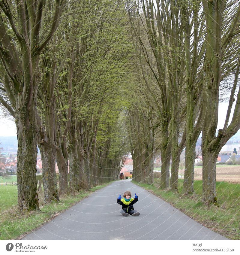 Kind sitzt mitten auf der unbefahrenen Straße einer Allee und hält die Daumen hoch Mensch Schulkind Asphalt sitzen Frühling Baum Feld Straßenrand Baumreihe
