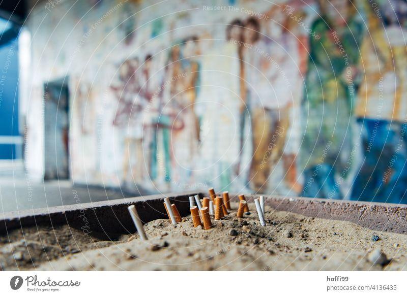 ausgedrückte Kippen im Sand vor bemalter Wand Zigarettenstummel Rauchen Tabakwaren Filterzigarette Zigarettenasche kippen ungesund Aschenbecher