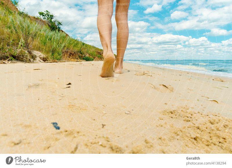 Mann läuft barfuß am Strand entlang in Richtung Stadt Erwachsener allein Bank Barfuß Badestrand Blauer Himmel Kaukasier Großstadt wolkig Tag Tageslicht Europäer