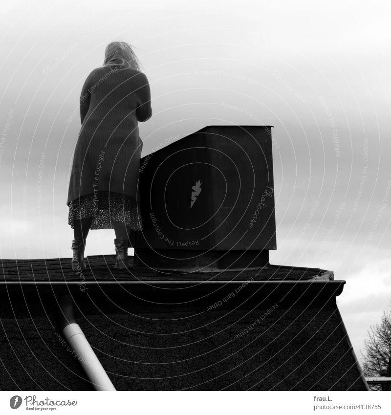 Eine Frau steht auf dem Dach Haus Himmel Baum blau Schornstein Regenrohr Rock Winter Mantel Rücken kalt