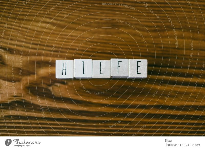 Das Wort Hilfe mit Buchstabenwürfeln auf Holz geschrieben helfen hilfreich Unterstützung SOS Hilfsbereitschaft Notfall Erste Hilfe Zuspruch füreinander Notruf