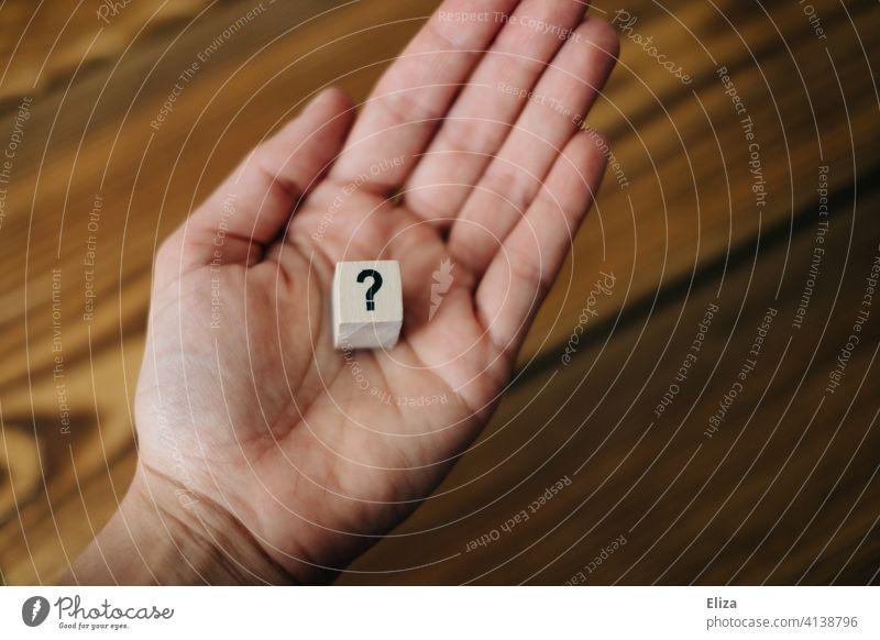 Hand hält ein Fragezeichen Unsicherheit ? fragend unsicher nicht wissen unwissenheit ratlos Ratlosigkeit Fragen