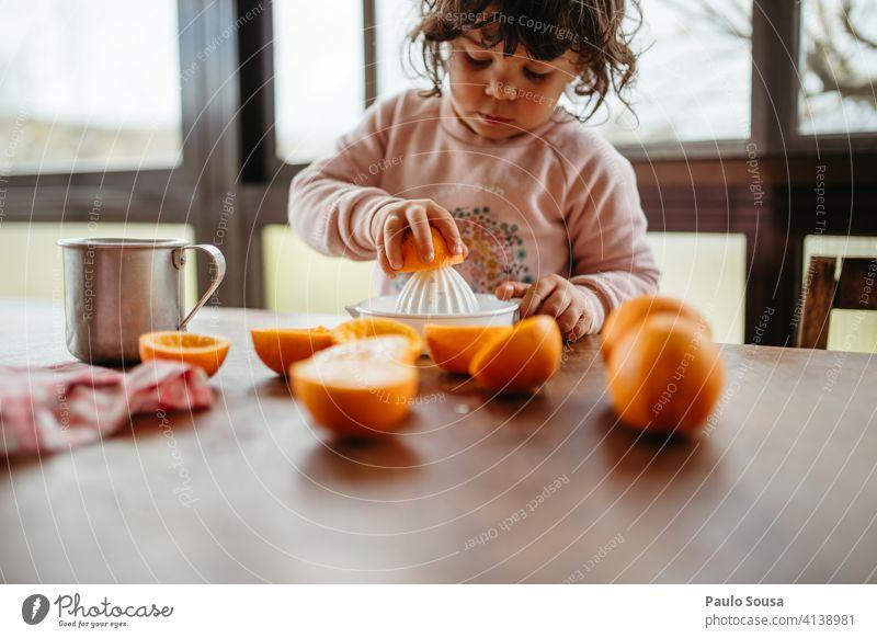 Kind macht Orangensaft zu Hause 1-3 Jahre Kaukasier Farbfoto authentisch orange Vorbereitung Frucht Mensch Kindheit Kleinkind Lifestyle Gesundheit mehrfarbig