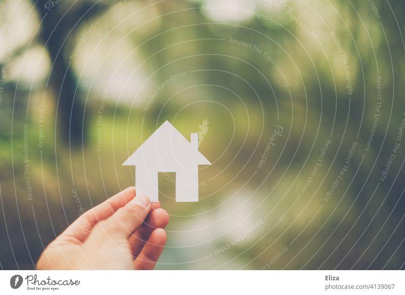 Hand hält ein weißes Haus aus Papier Hausbau Immobilie Eigenheim Zuhause Hauskauf Traumhaus Natur Mensch Bausparen häuslich Haus bauen Heim wohnen Papierhaus