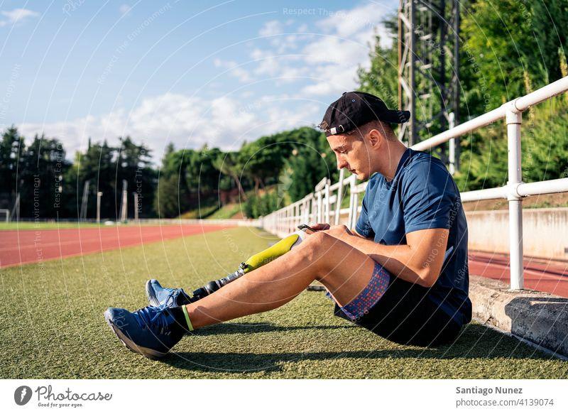 Behinderter Sportler beim Telefonieren per Telefon Mann Läufer Athlet Prothesen Prothetik Behinderung deaktiviert Typ Tippen Amputation Amputierte Mitteilung
