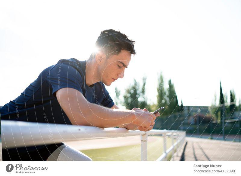 Behinderter Sportler beim Telefonieren Stehen Athlet per Telefon Tippen Junge jung Porträt Sportbekleidung Seitenansicht Mann Läufer Mitteilung Smartphone
