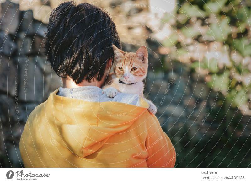 Rückenansicht eines Kindes mit Kätzchen Katzenbaby Haustier Haustiere Liebe heimisch Irrläufer heimatlos bezaubernd Menschen Kleinkind Baby verirrt im Freien