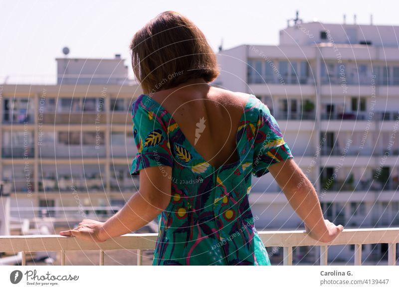 Frau auf einem Balkon an einem sonnigen Morgen Junge Frau Sonnenlicht im Innenbereich Quarantäne Einsperrung Isolation vereinzelt Coronavirus Pandemie