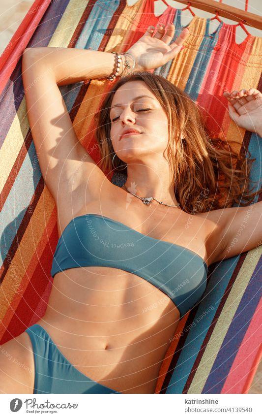 Junge Frau im blauen Badeanzug liegt in einer Hängematte bei Sonnenuntergang Lügen gestreift tropisch Lifestyle Sommer jung Kaukasier Mode allein im Freien