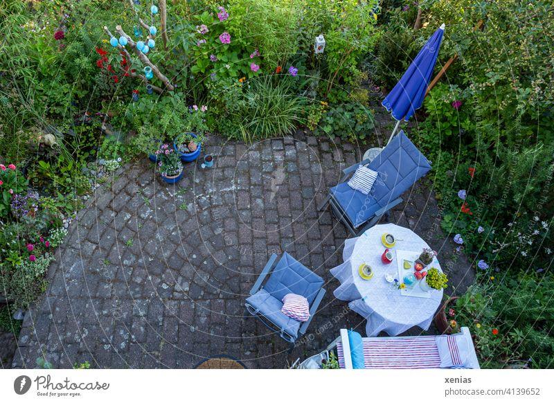 Vogelperspektive im Sommer: Zwei gelbe Tassen Kaffee auf dem Tisch, Stühle mit gemütlichen Kissen und Sonnenschirm stehen auf der Terrasse bereit. Diese ist umgeben von grünen Pflanzen mit bunten Blüten. Wo sind die Kaffeetrinker hin?