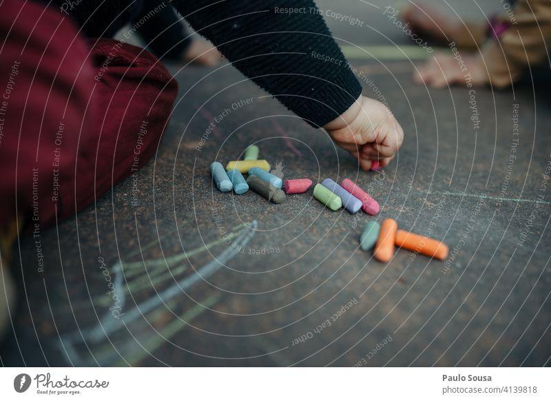 Kind zeichnet mit farbiger Kreide auf dem Boden Nahaufnahme 1-3 Jahre Kreidezeichnung zeichnen Kindheit Spielen Kunst Außenaufnahme Freizeit & Hobby