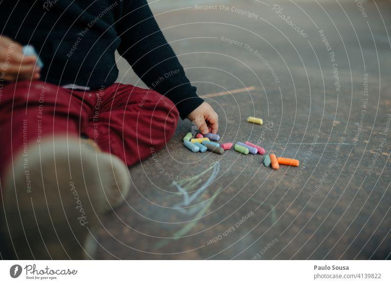 Close up Kind spielt mit Kreide Kreidezeichnung Zeichnung Kindheit Asphalt Strassenmalerei Kinderspiel malen Freizeit & Hobby Spielen Straßenkreide Farbfoto