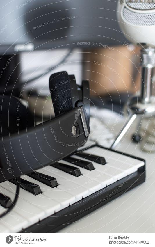 Einrichtung des Computertisches eines Musikers: Tastatur, Kopfhörer und Mikrofon vor einem Monitor Gerät dj Audio Technik & Technologie Klang Atelier Büro