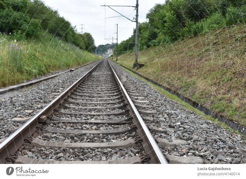 Bahngleise im Graben, gesäumt von Strommasten, die sich in die Ferne erstrecken. Hintergrund Spalte Konzept Tag Regie Entfernung entfernt elektrisch weit Kies