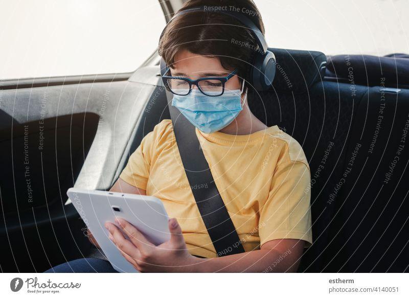 Kind mit medizinischer Maske fährt in einem Auto Coronavirus Virus medizinische Maske Tablette PKW KFZ Sicherheitsgurte Seuche Pandemie Quarantäne Familie