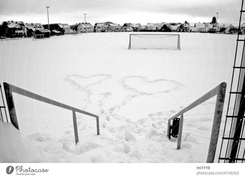 zwei Herzen im Schnee Fußballplatz Tor Geländer Winter Liebe Verliebt Verliebtheit Zeichen Zuneigung zeigen Gefühle symbolisieren Fußballtor schneebedeckt