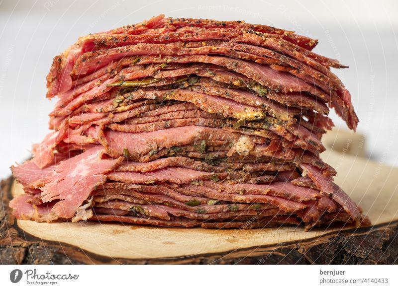 Scheiben vom geschnittenem Pastrami-Fleisch Rindfleisch brisket rustikal FleischScheiben Stapel Nahaufnahme rot Deli schneiden kalt gefaltet dünn geröstet Essen