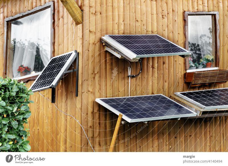 Kleingartenidylle: Solarpaneele am Gartenhaus schrebergarten menschenleer pflanze Hecke Paneele Holzhaus Fensterrahmen Blumentopf Solarenergie Solarmodul