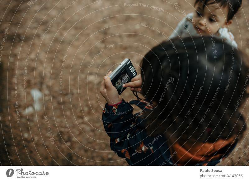 Kind spielt mit Digitalkamera 1-3 Jahre Kaukasier Geschwister Familie & Verwandtschaft Fotokamera Fotografie digital Technik & Technologie Außenaufnahme