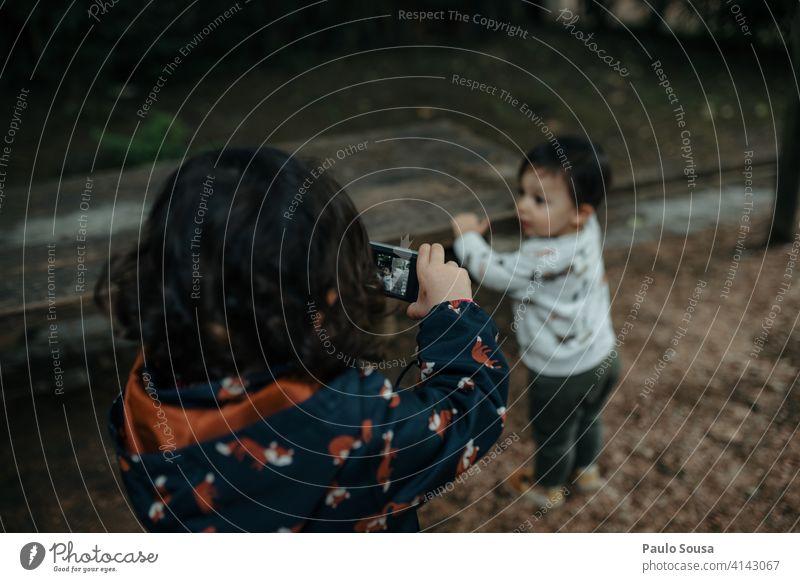 Junges Mädchen, das ein Foto von ihrem kleinen Bruder macht Geschwister Kind 1-3 Jahre Kaukasier Kindheit digital Digitalfotografie Fotokamera