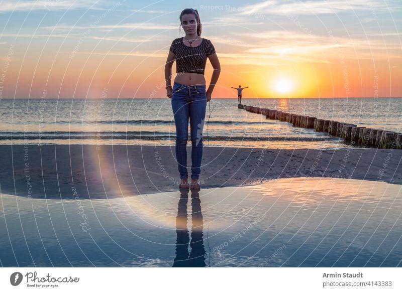 Sonnenuntergang über der Ostsee, Porträt einer jungen Frau, die am Strand steht Ausgewogenheit schön Schönheit Junge Abenddämmerung weit Freiheit Mädchen Leiste