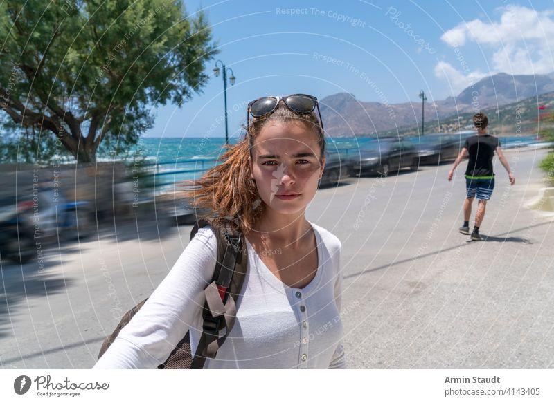 Selfie einer schönen jungen Frau im Urlaub Rücken Rucksack blau Unschärfe Junge Autos lässig Kaukasier selbstbewusst Laufwerk Außenseite Mädchen wandern Reise