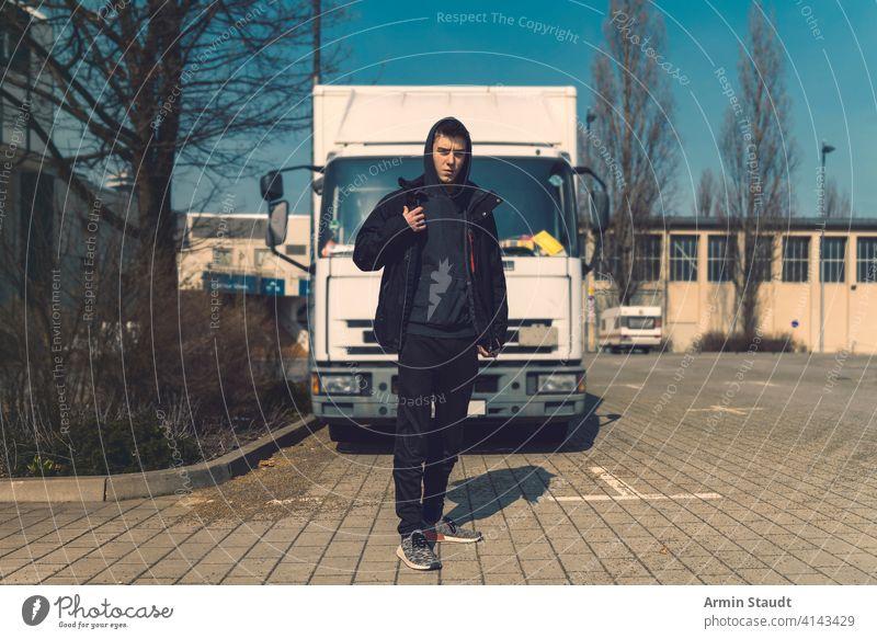 junger Mann mit Rucksack steht vor einem Lastwagen aeria Architektur schön schwarz Junge Gebäude lässig Kaukasier selbstbewusst Kapuzenpulli Lifestyle Blick