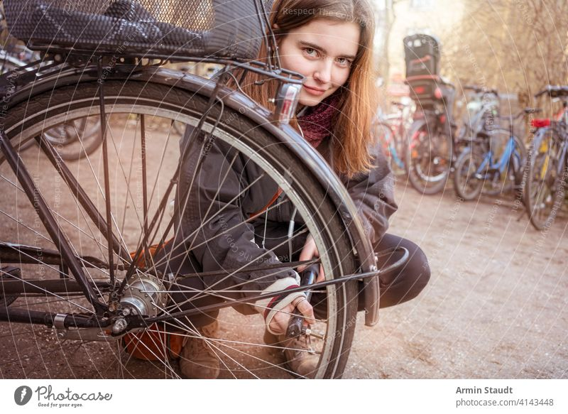 Junge Frau pumpt die Reifen ihres Fahrrads auf Aktivität Air lässig Kaukasier Nahaufnahme selbstbewusst hockend Details Gerät fixieren Mädchen Lifestyle Makro