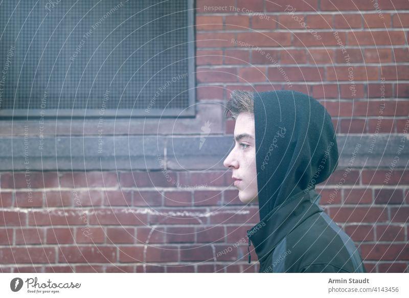 Porträt eines jungen Mannes im Profil mit Kapuzenpulli schön Junge Baustein lässig Kaukasier selbstbewusst cool gehen gutaussehend Bild Lifestyle Blick männlich