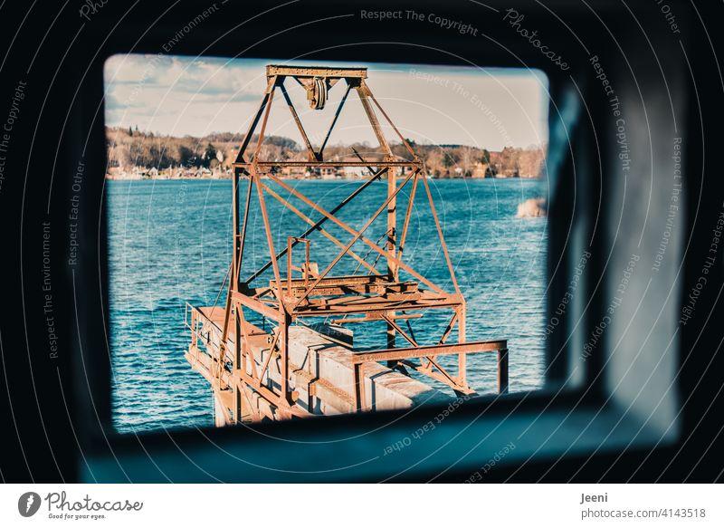 Ausblick aus dem kaputten Fenser des alten Hafenspeichers auf die verrostete und in die Jahre gekommene Krananlage Blick ausblick Fenster fensterlos Loch blau